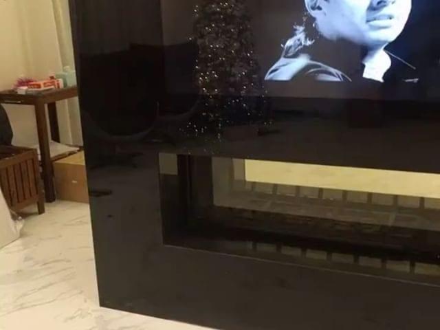 На данном объекте клиент пожелал обыграть настоящий камин телевизором Burg&Glass в черном стекле